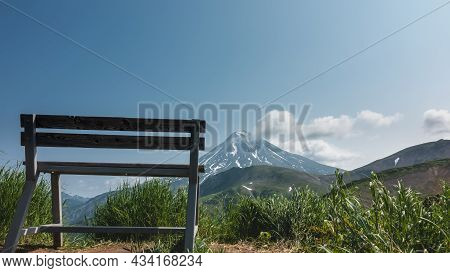 On The Top Of The Hill, Among The Green Grass, There Is A Wooden Bench. Ahead, Against The Blue Sky,