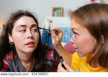 Two Young Women Make Up Decorative Cosmetics. One Woman Paints Another Woman's Eyelashes With Mascar