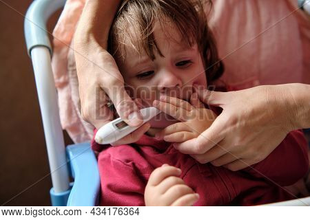 Mother Measures The Temperature Of Her Little Daughter, The Girl Is Sick, She Has A Fever. Scared Li