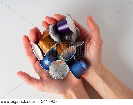 10.03.2021 Russia, Moscow. Women's Hands Hold Colorful Aluminum Capsules For Nespresso Coffee Machin