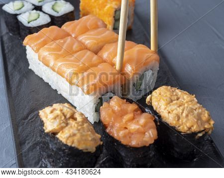 A Variety Of Japanese Rolls And Sushi On A Textured Black Plate. Side View. Bamboo Chopsticks Holdin