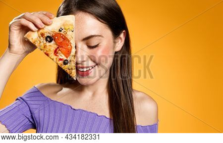 Smiling Romantic Woman Holding Slice Of Pizza Near Her Face, Looking Down Sensual, Advertising Pizze