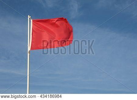 Big Red Flag On The Blue Sky Symbol Of Danger And Hazard