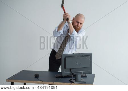 Stressed Crazy Businessman Smashing His Computer In Office Using Ax Problem Concept. The Man Has Pro