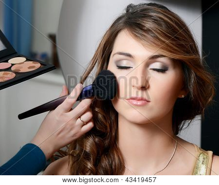 Beautiful girl put the makeup on the face