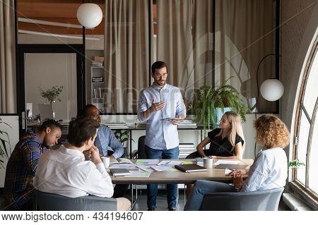 Confident Business Team Leader Speaking To Employees At Corporate Meeting