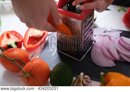Woman Grates Vegetables In Kitchen. Preparing Vegetables For Lunch Meals