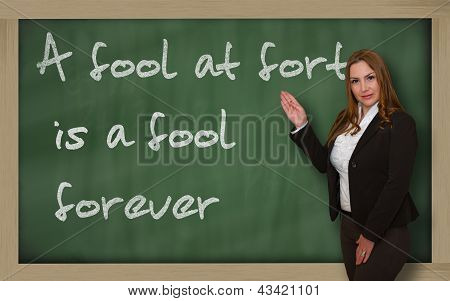 Teacher Showing A Fool At Forty Is A Fool Forever On Blackboard