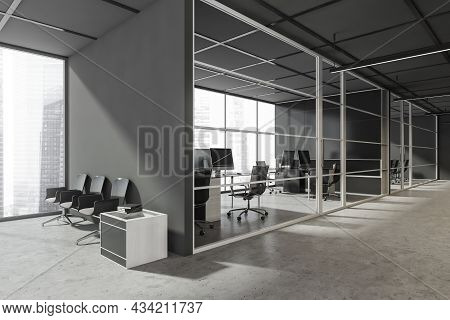Grey Office Lobby With The Seating Next To An Empty Wall, Concrete Flooring, A Frame Glass Partition