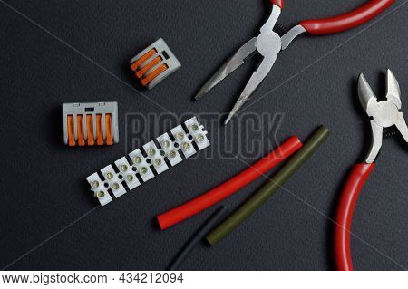 Tools For Working With Electricity, Terminal Blocks And Heat Shrink Tubes Lie On A Dark Background