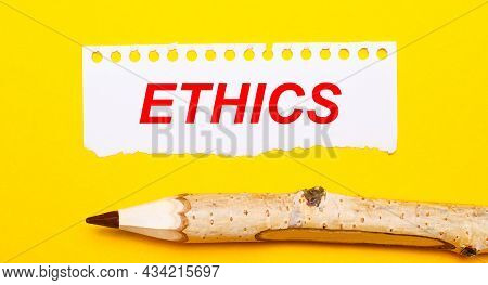 On A Bright Yellow Background, A Large Wooden Pencil And A Sheet Of Torn Paper With The Text Ethics