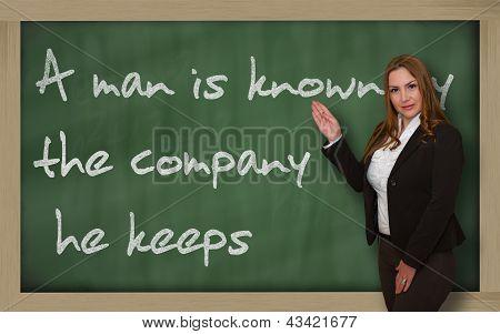 Teacher Showing A Man Is Known By The Company He Keeps On Blackboard