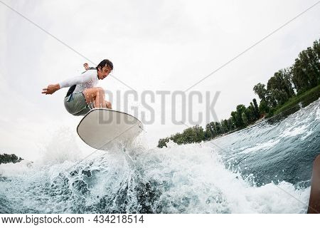 Young Sportsman Effectively Jumps On Wakeboard Over Splashing Wave.