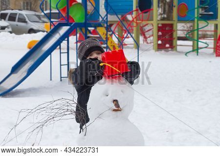 A Boy On The Playground In Winter Makes A Snowman Out Of Snow With A Red Bucket On His Head.