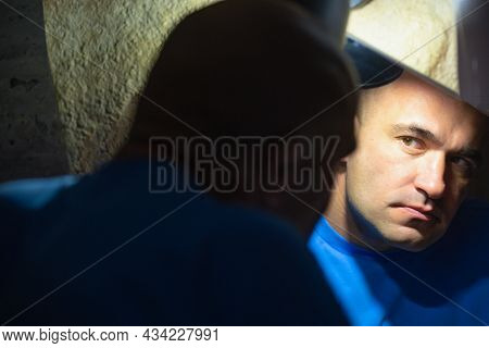 A Man In The Dark Looks At Himself In The Mirror. Bright Lamp Lighting.