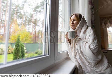 Pensive Young Woman In Sweater Drinking Hot Purifying Herbal Tea At Home. Thoughtful Girl Drinking C