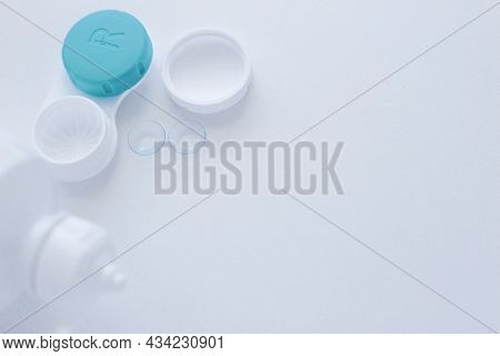 A Lens Container, A Lens Storage Liquid And Two Contact Lenses Lie On The Side On A White Background