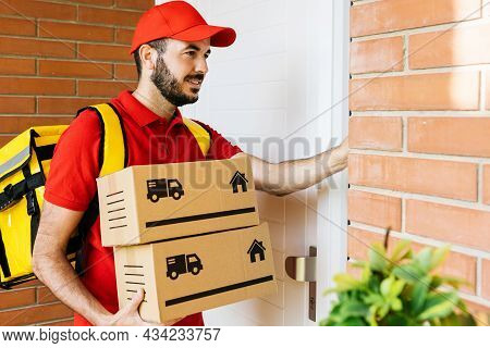 Happy Delivery Man In Red Uniform With Backpack Ringing The House Doorbell While Holding Cardboard B