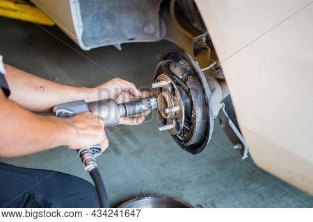 Repair Mechanic Hands During Maintenance Work To Pneumatic Gun To Loosen A Wheel Nut Changing Tyre O