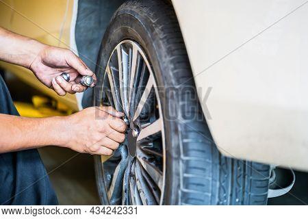 Repair Mechanic Hands During Maintenance Work To Loosen A Wheel Nut Changing Tyre Of Car, Man Fixing