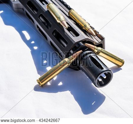 A Ar15 Rifle Barrel And Muzzle With 223 Caliber Ammunition Next To It On A White Background