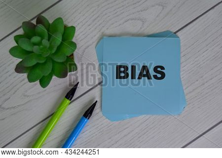 Bias Write On Sticky Notes Isolated On Wooden Table.