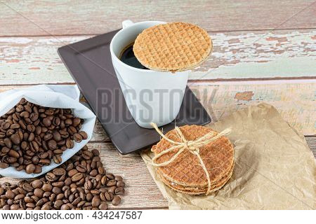 Stroopwafel Cookies Over A Cup Of Coffee Next To Roasted Beans.
