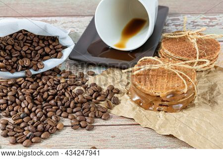 Closeup Of Stroopwafels Stacked On Brown Paper, Next To A Cup Of Coffee Lying Down.