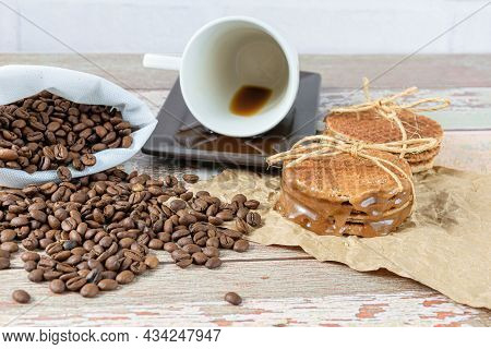 Stroopwafels Stacked On Brown Paper, Next To A Lying Coffee Cup.