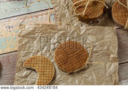 Stroopwafel With A Bite On Brown Paper Next To Another Cookie And Sisal String.
