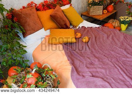 Home Autumn Decor. Cozy Fall Bedroom Interior Bed With Orange Pillows And Pumpkins, Autumn Decoratio
