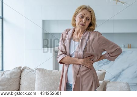An Elderly Woman Feels Back Pain While Massaging Aching Muscles While Standing In The Living Room