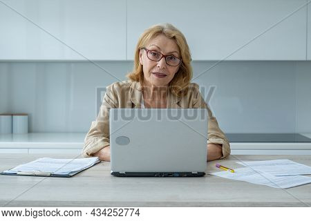 Happy Elderly Woman With Glasses And Looking At The Camera At Home. A Successful Elderly Lady Works