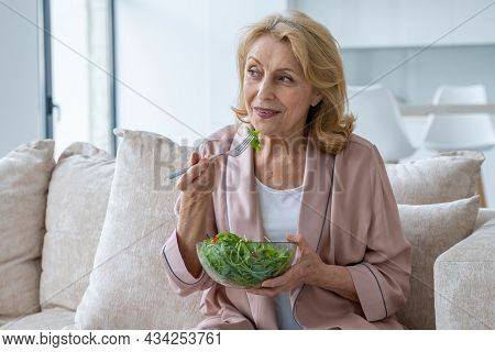 Beautiful Elderly Woman Eats Her Vegetable Salad Sitting At Home On The Couch