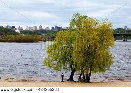 Fisherman Catches A Fish Near A Tree On A Sandy Beach. Cloudy Landscape Of Kyiv. Rainy Weather In Th