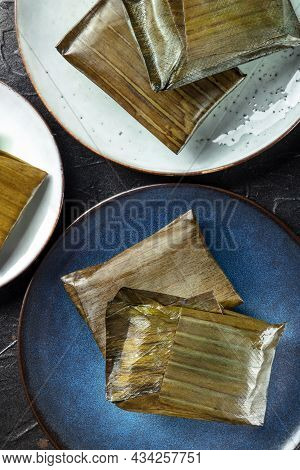 Tamales Oaxaquenos, Traditional Hispanic Dish, Wrapped In Green Leaves, Shot From The Top On A Black