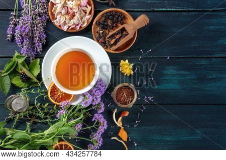 Tea Banner With Herbs, Flowers And Fruit, Top Shot On A Dark Rustic Wooden Background With Copy Spac