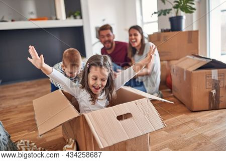 A young family is playing in a cheerful atmosphere in the new home they have just moved in. Home, family, moving