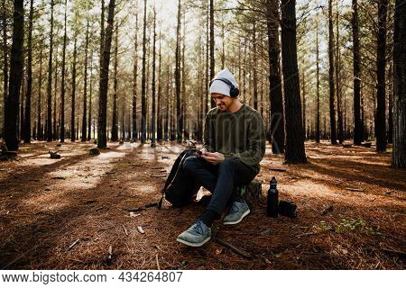 Caucasian Male Relaxing Listening To Music With Headphones Texting Friends On Smartphone Sitting In