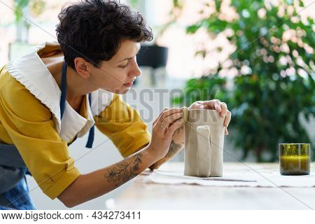Creative Young Woman Shaping Clay Jug In Studio. Female Artist With Tattoos On Hands Work On Pottery