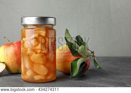Tasty Apple Jam In Glass Jar And Fresh Fruits On Grey Table, Space For Text