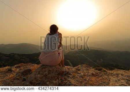 Back View Portrait Of A Woman Alone Contemplating Sunset In The Mountain