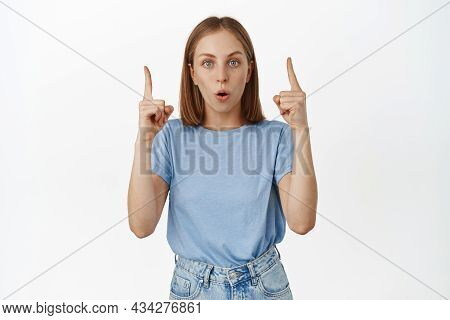Portrait Of Surprised Young Woman Stare Impressed, Pointing Fingers Up At Awesome Discount, Showing