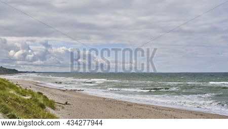 Beautiful Seascape With Waves, Old Wooden Breakwater, Sandy Beach And Cloudy Sky. Baltic Sea, Curoni