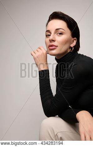Confident Portrait Of Beautiful Fashionable Attractive Brunette European Woman Sitting Three Quarter