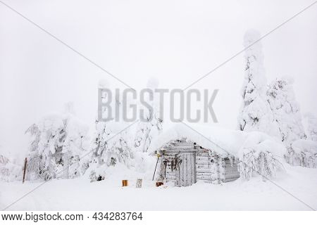 Snow covered log cabin in majestic winter forest in Lapland Finland