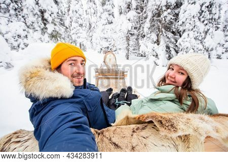 Happy couple on reindeer safari in winter forest in Lapland Finland