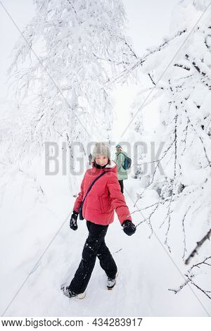 Cute pre-teen girl enjoying time with her family in winter forest among snow covered trees in Lapland Finland