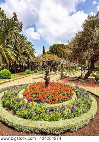 Luxurious flower bed with bright red flowers. Bahai World Center. Pilgrimage center and popular tourist destination. The slope of Mount Carmel. Haifa, Israel.