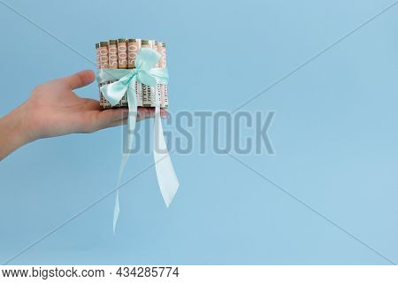 Female Hand Holding Ukrainian 500 Banknotes In Rolls Tied With A Gift Ribbon.
